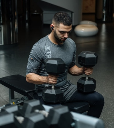 Photo of a young man, with a beard, holding two large dumbbells in a gym.