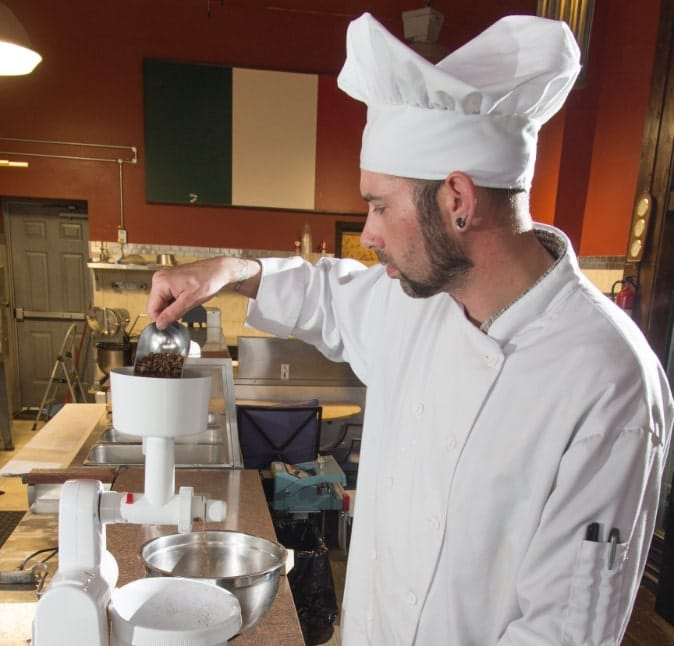 Photo of an Entomo Farms team member grinding crickets, wearing a chef's jacket and hat