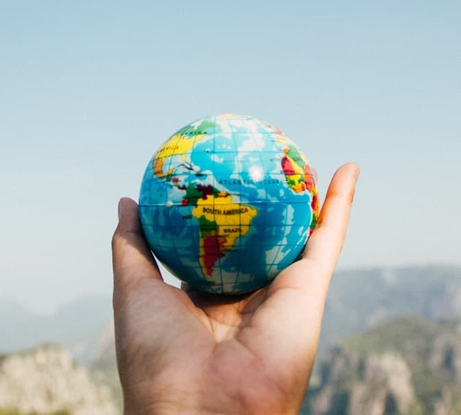 Photo of a hand holding up a small globe.